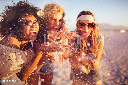Mixed race group of girls blowing colourful confetti from their hands happily on a beach at sunset