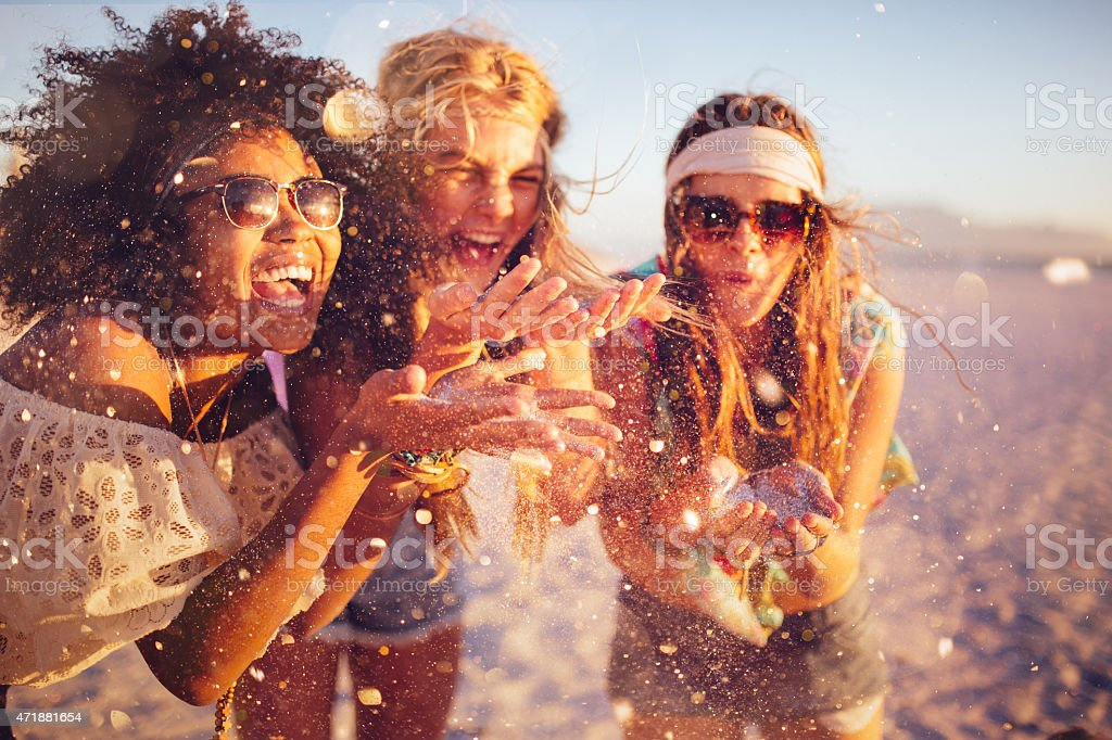 Girls blowing confetti from their hands on a beach stock photo