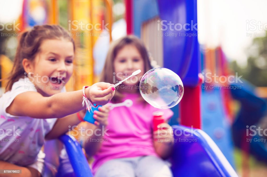 Mädchen bläst Seifenblasen im Park – Foto
