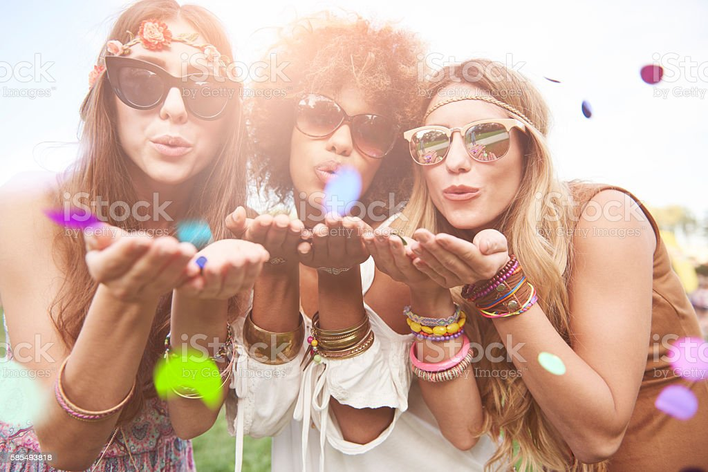Girls blowing some confetti pieces stock photo