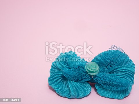 girls blue hair tie bow clip on pink background. closeup shot with color contrast and lot of copy space