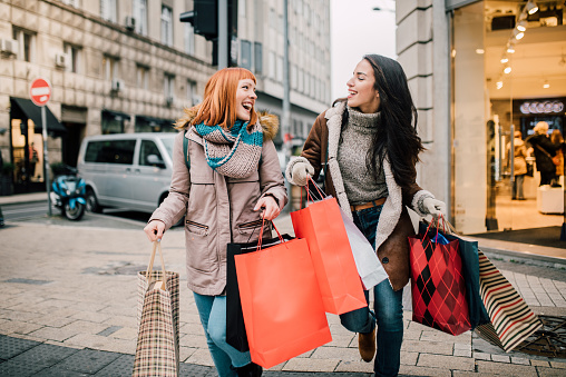 Happy two girls holding bunch of shopping bags