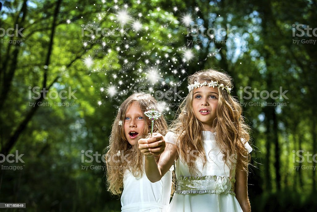 Girls casting magic spells in woods. stock photo