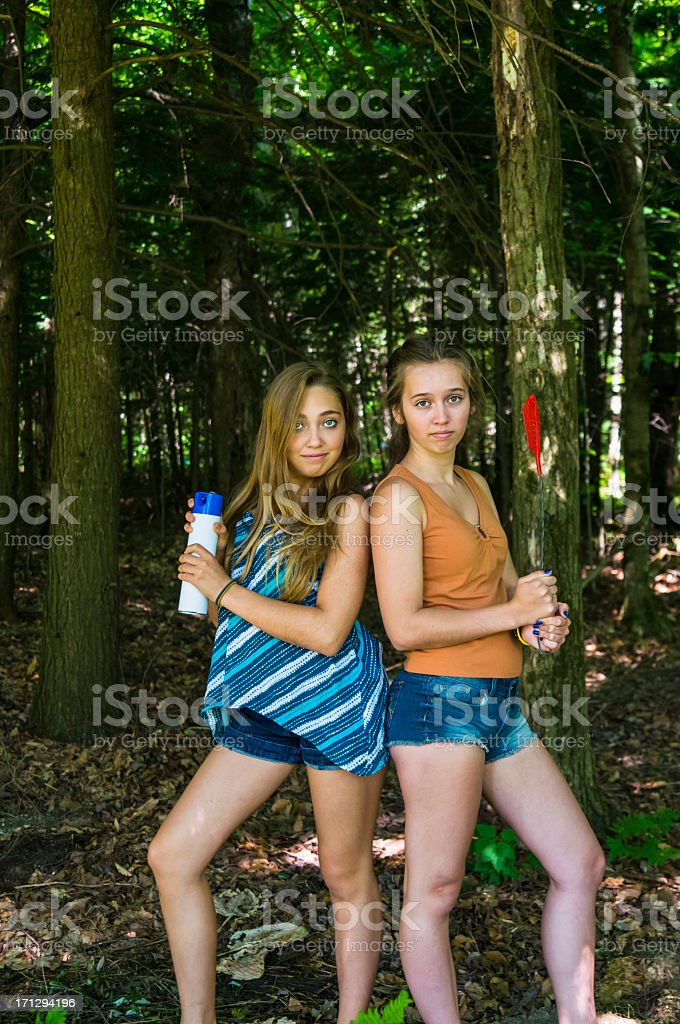 Girls chasing bugs in the forest, vertical. stock photo