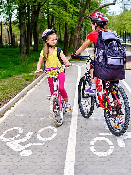 Girls children cycling on yellow bike lane. – Foto