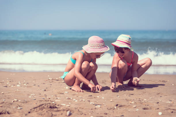 girls collecting sea shells on the beach - little girl picking up sea shells at the beach stock pictures, royalty-free photos & images