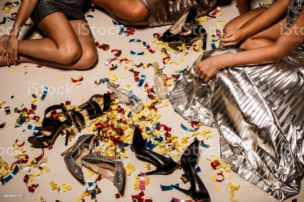 Girls, confetti, shoes and bottles on the floor after party stock photo