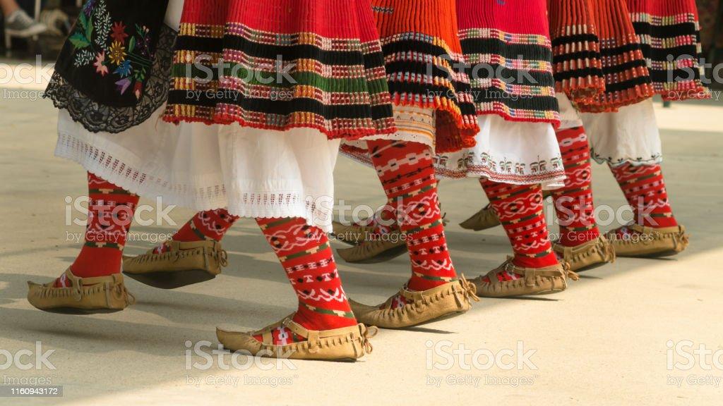 Girls dancing folk dance. People in traditional costumes dance...
