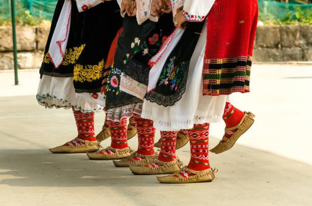 meisjes dansen folk dance. mensen in traditionele kostuums dansen bulgaarse volksdansen. close-up van vrouwelijke benen met traditionele schoenen, sokken en kostuums voor volksdansen. - bulgarije stockfoto's en -beelden