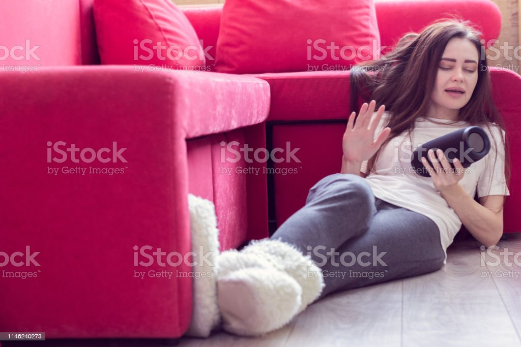 the girl is sitting on the floor and listening music from portable...