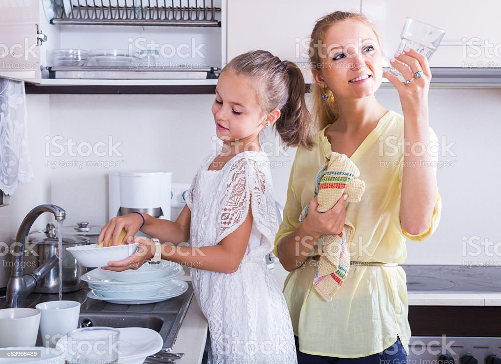 girls doing and wiping dishes in kitchen stock photo