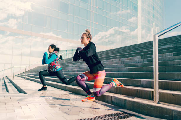 Girls doing frontal lunges at the steps outside stock photo