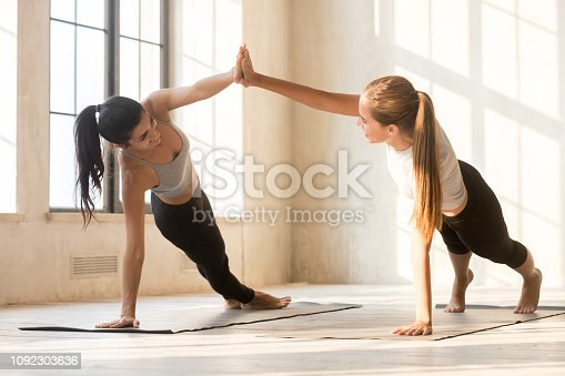 Young attractive blond and brunette diverse multi-ethnic women practicing yoga together giving high five holding hands and standing in side plank pose on rubber mats at fitness studio in the morning