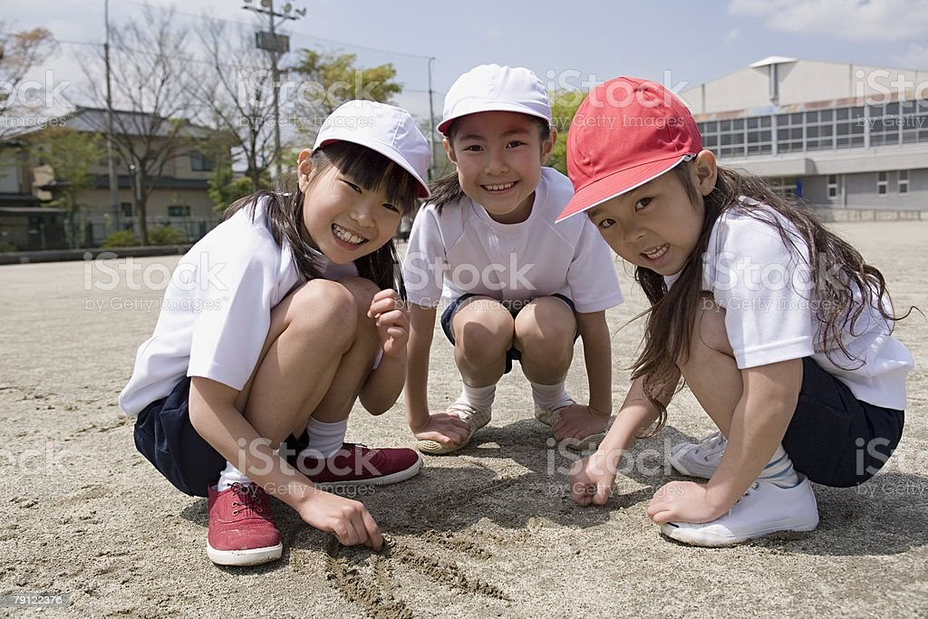 Girls drawing in the sand 免版稅 stock photo