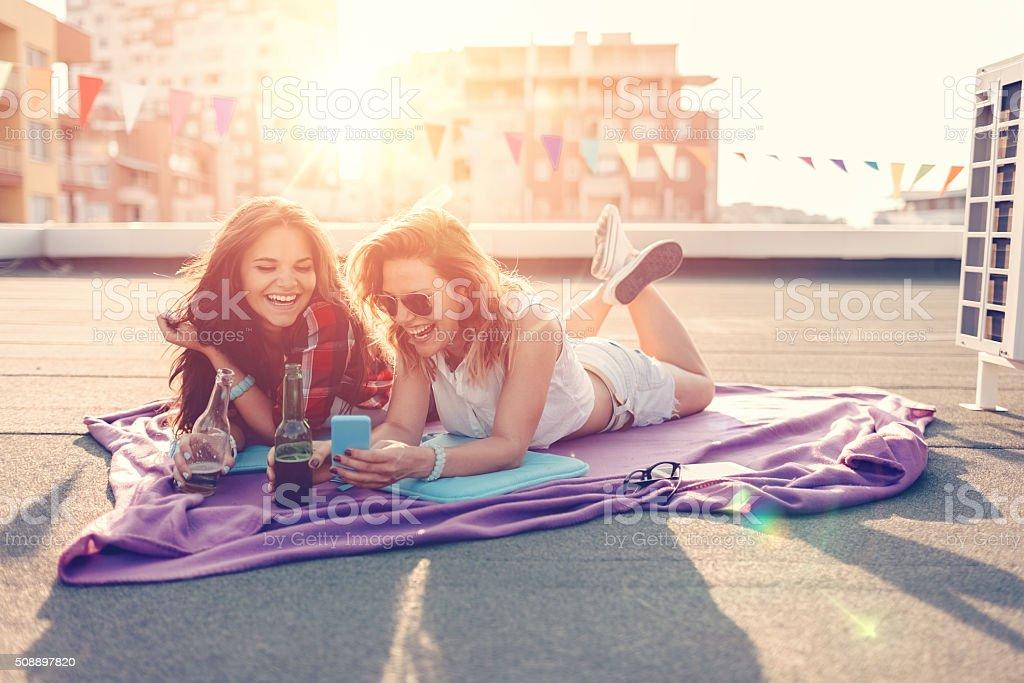 Meninas tomando uma cerveja na cobertura - foto de acervo