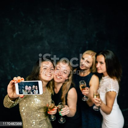 Hen party. Girls holding glasses with champagne, congratulating friend. Women taking selfie together