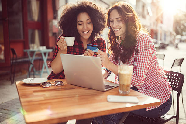 Girls drinking coffee and shopping online stock photo