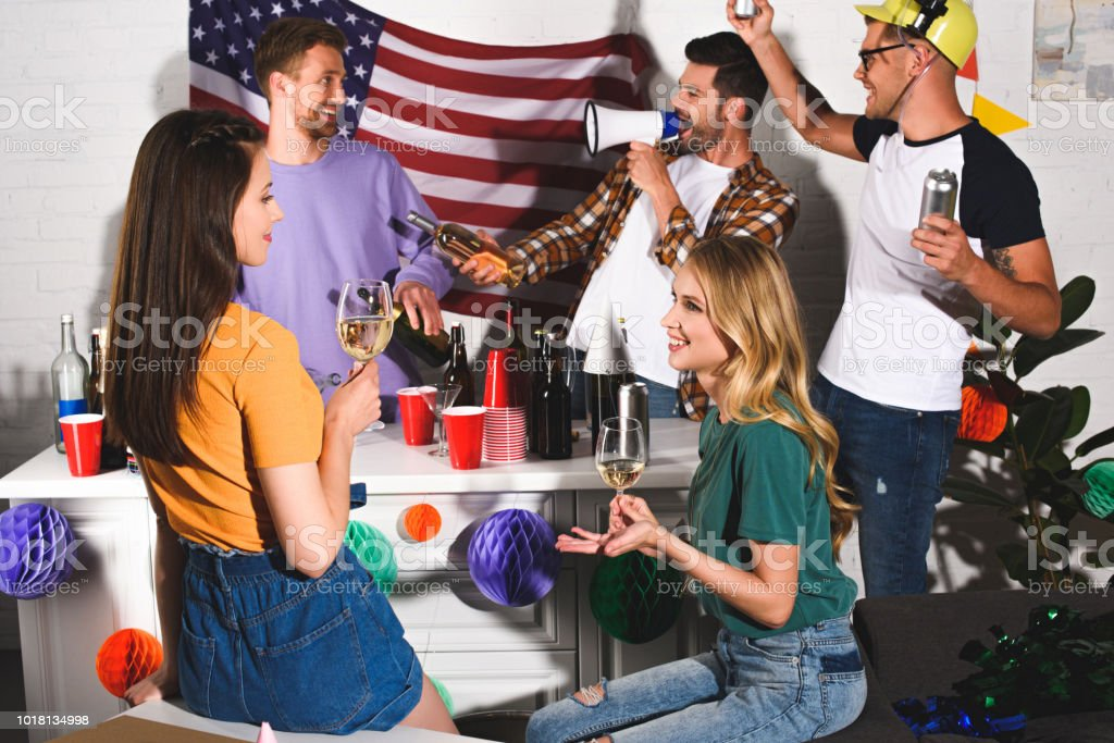 girls drinking wine and smiling each other while men partying behind stock photo