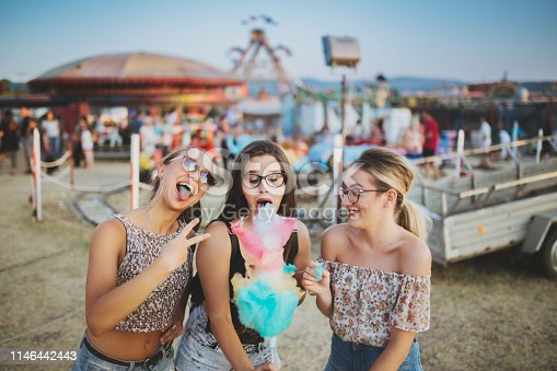 Girls having fun with cotton candy at the county fair in summer