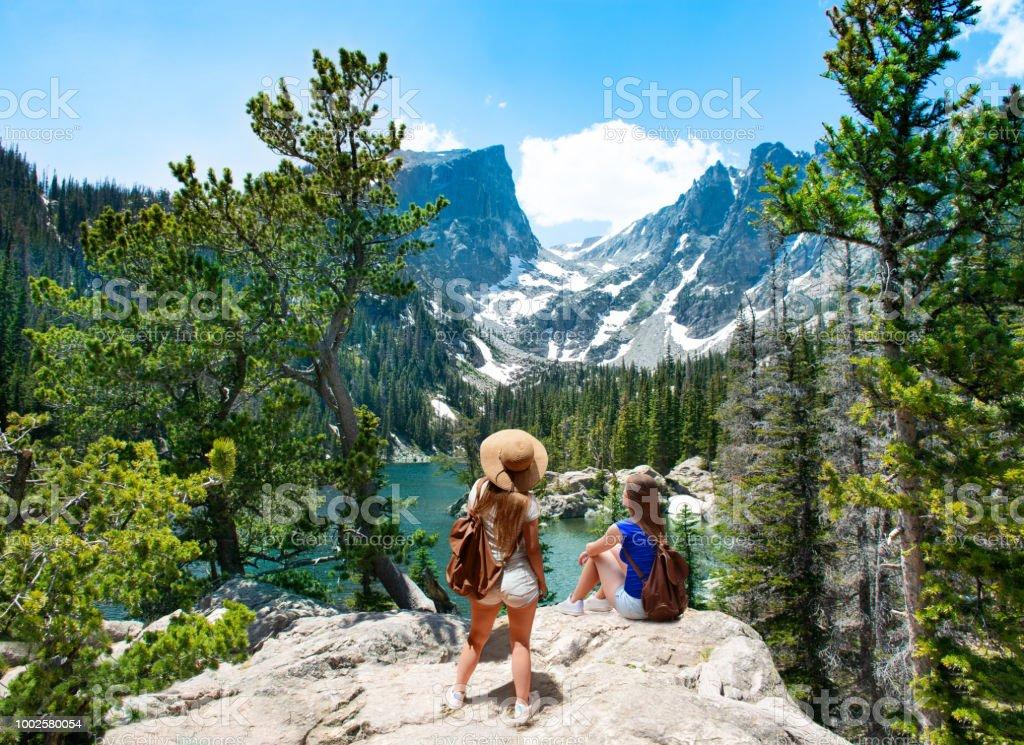 Girls enjoying beautiful view on hiking trip in the beautiful mountains. stock photo
