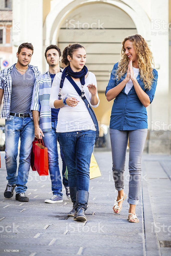 Girls Enjoying Shopping with Bored Boyfriends Behind stock photo