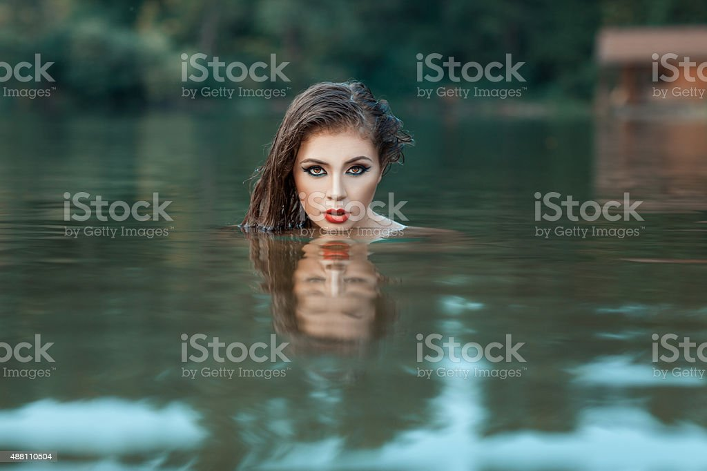 Girl's face peeking out of the water. stock photo