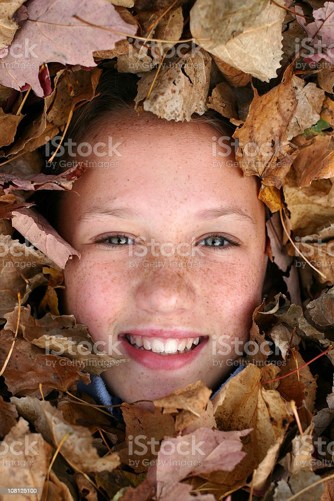 Girl's Face Surrounded by Autumn Leaves royalty-free stock photo