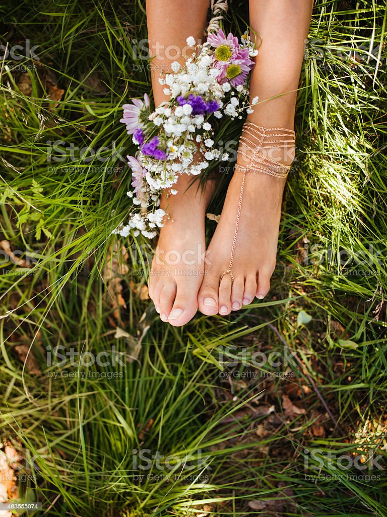Girl's feet in green grass with flowers and foot jewellery stock photo