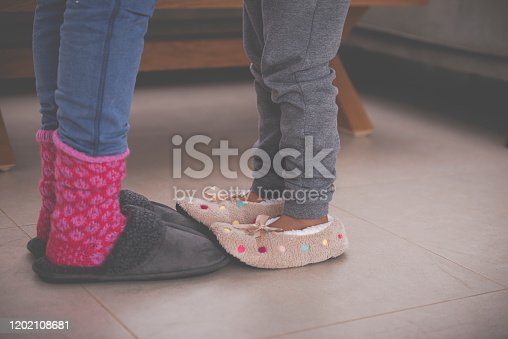 Close up image of girl's feet in slippers stepping on mother's feet. The daughter wearing slippers decorated with polka dots and woman wearing red warm woolen socks and dark gray slippers.
