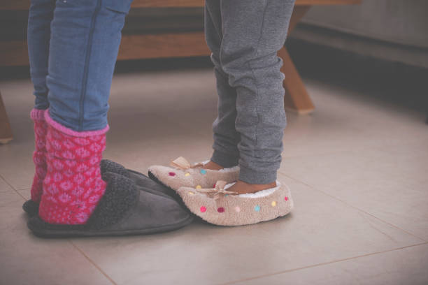 Girl's feet in slippers stepping on mother's feet. stock photo