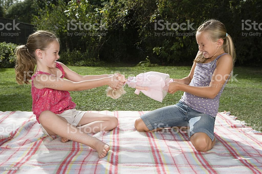 Girls fighting over doll stock photo