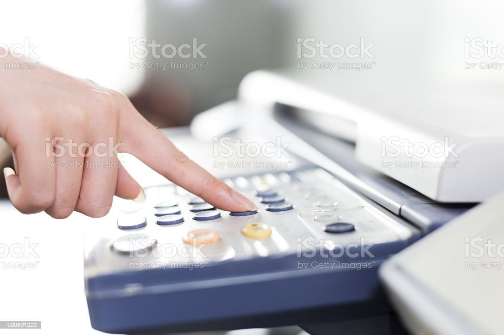 girl's finger presses button of copier stock photo