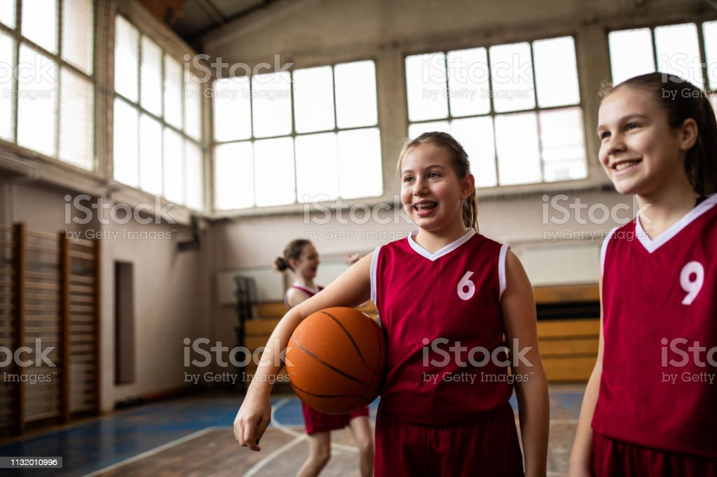 Satisfied teenage girls walking and holding basketball ball after...