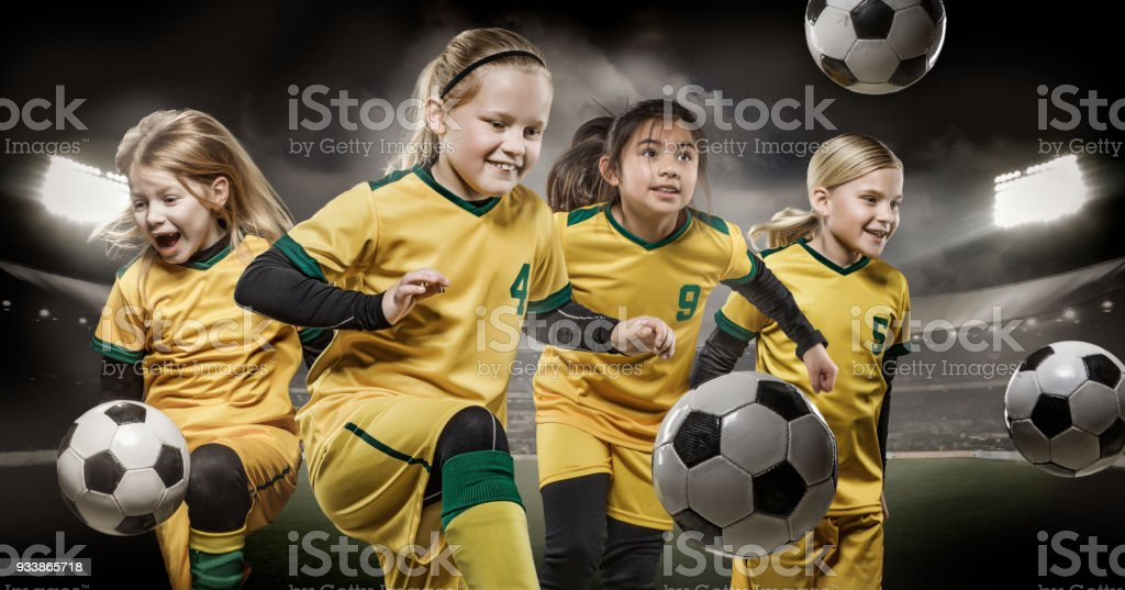 Girls football team posing for action soccer team photos in a...