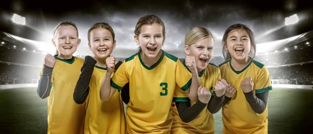 Girls football team posing for soccer team photo in a floodlit stadium stock photo