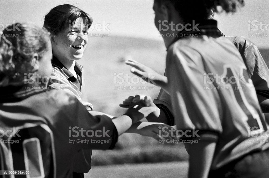 Girls football team with hands together, outdoors (B&W) royalty-free stock photo