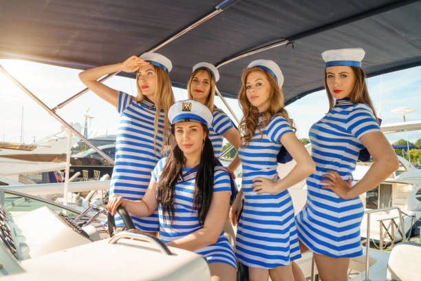 Girls friends are at the helm of the yacht in striped dresses and caps stock photo