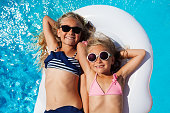 Top view portrait of two age-diverse girls, happy friends in sunglasses and bikini, sunbathing on inflatable mattress in swimming pool