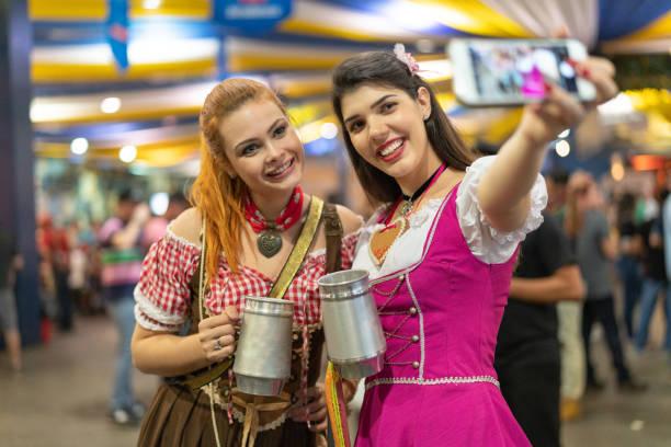 mädchen freunde nehmen einen selfie auf festlichen toast auf dem oktoberfest - moderne dirndl stock-fotos und bilder