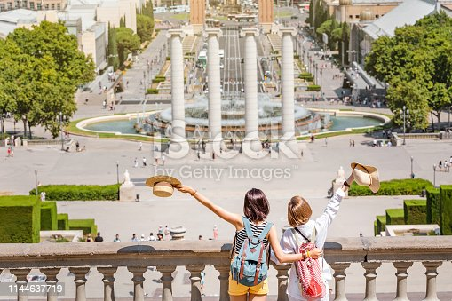 istock Girls friends with backpacks hug and enjoy the view of Placa de Josep Puig i Cadafalch in Barcelona, Catalonia 1144637719