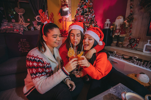 Friends have fun and drink a cocktail at a Christmas party.