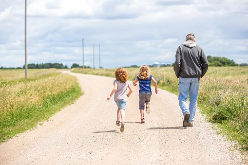 Girls & Grandpa Walking & Running Out Rural Gravel Driveway