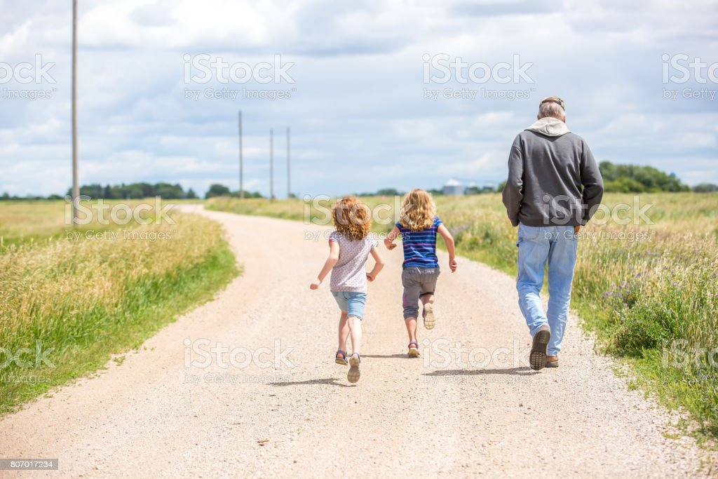Girls & Grandpa Walking & Running Out Rural Gravel Driveway stock photo