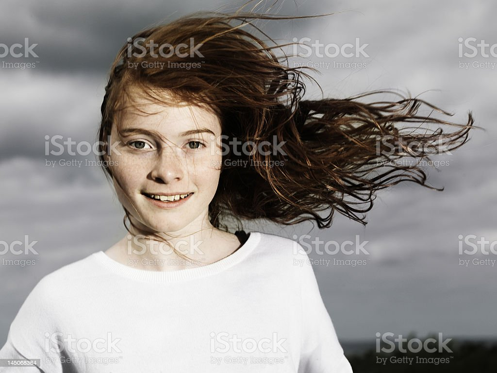 Girls hair blowing in wind outdoors stock photo