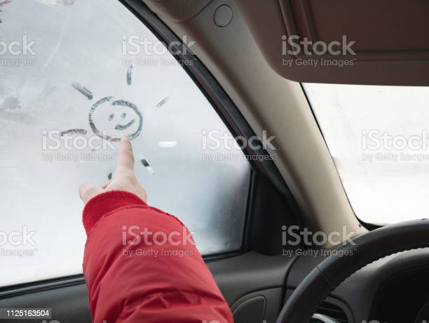 Photo of girls hand draw sun on car window