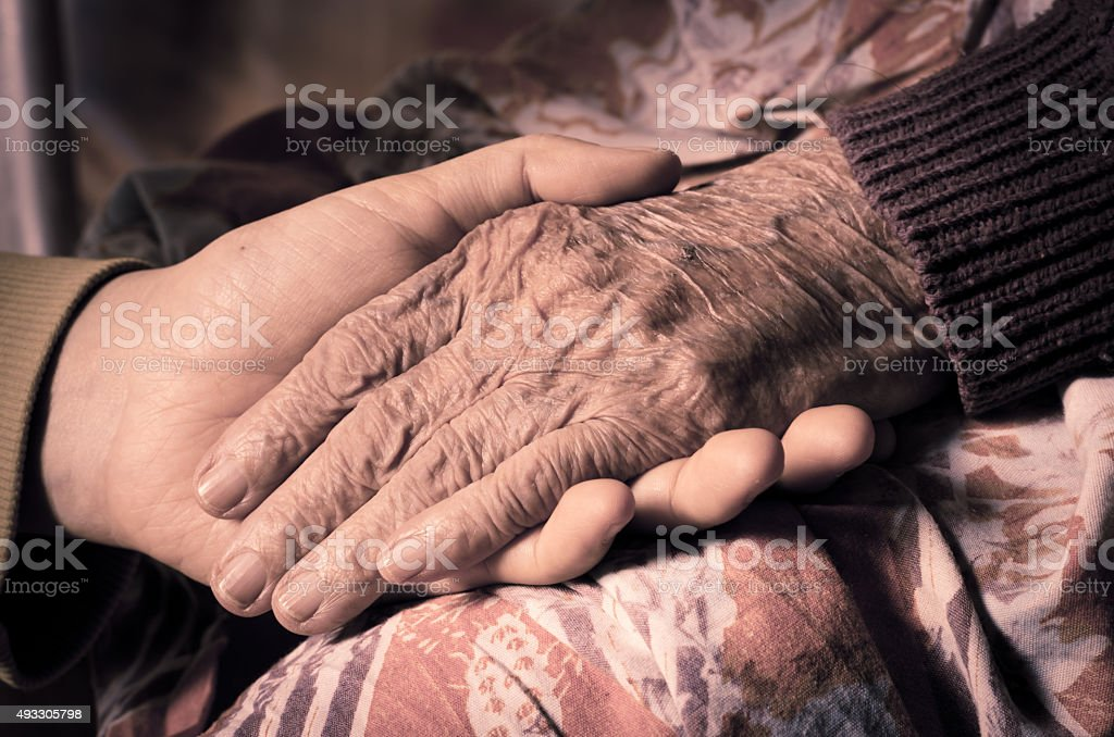 girl's hand holds an old woman's hands stock photo