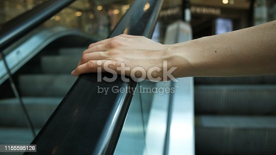 Girl's hand on escalator handrail in shopping center, close-up, girl rises up to go shopping