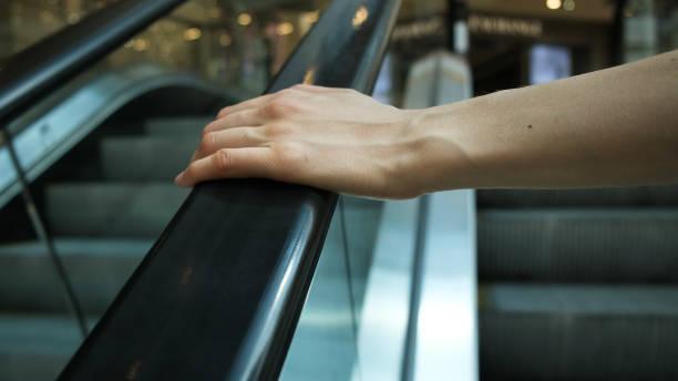 girl's hand on escalator handrail in mall, close-up - escalator foto e immagini stock