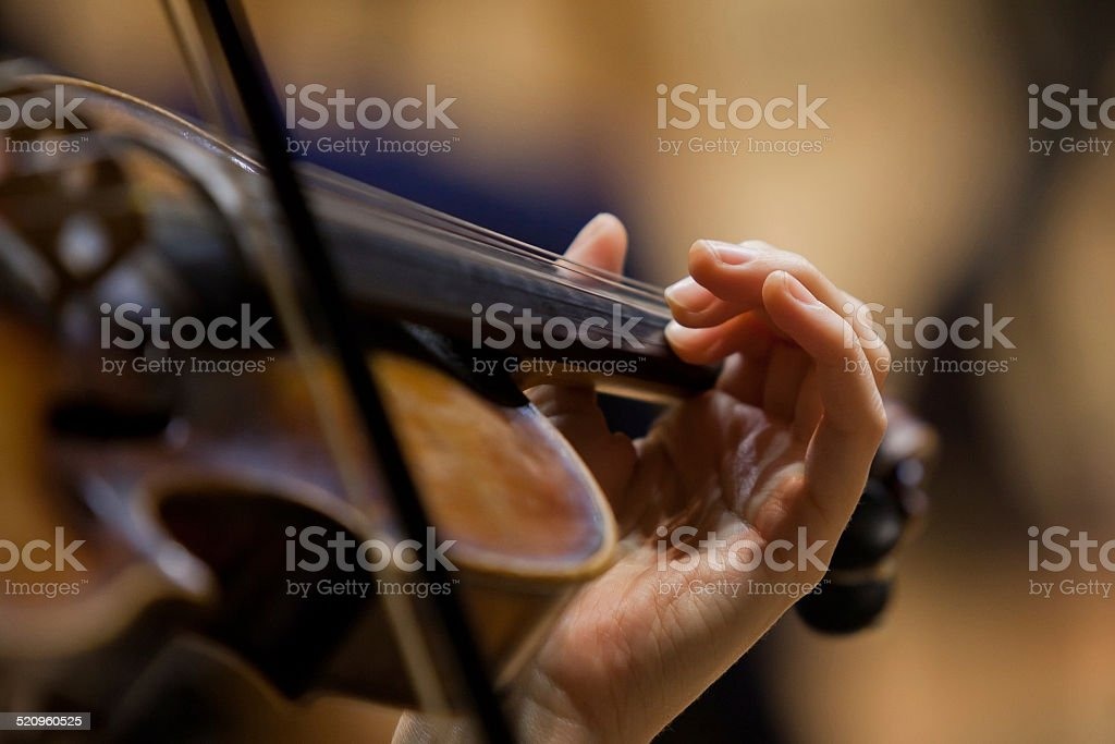 Girl's hand on the strings of a violin stock photo