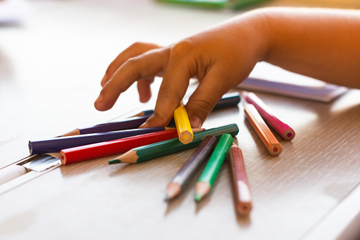 Mano de niña cogiendo colores para pintar en un tren